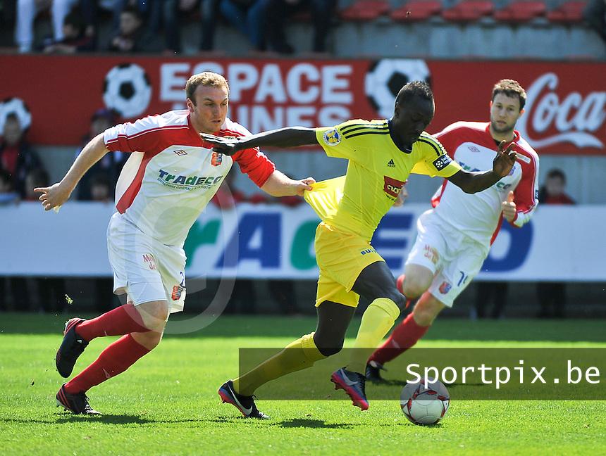 Moeskroen Peruwelz - SK Sint-Niklaas  : Ameth Gaye aan de bal voor de trekkende Kevin Vandendriessche (links).foto VDB / BART VANDENBROUCKE