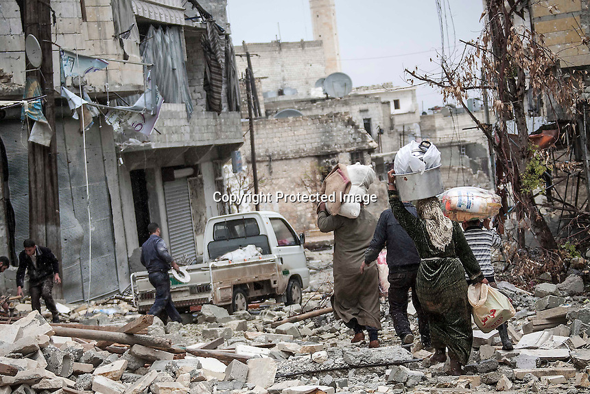 In this Tuesday, Dec. 11, 2012 photo, rain falls as Syrian residents collect their belongings after their houses were damaged due to fighting between Free Syrian Army and government forces, while heavy artillery explosions are heard in the battlefield of Aleppo, Syria. (AP Photo/Narciso Contreras)