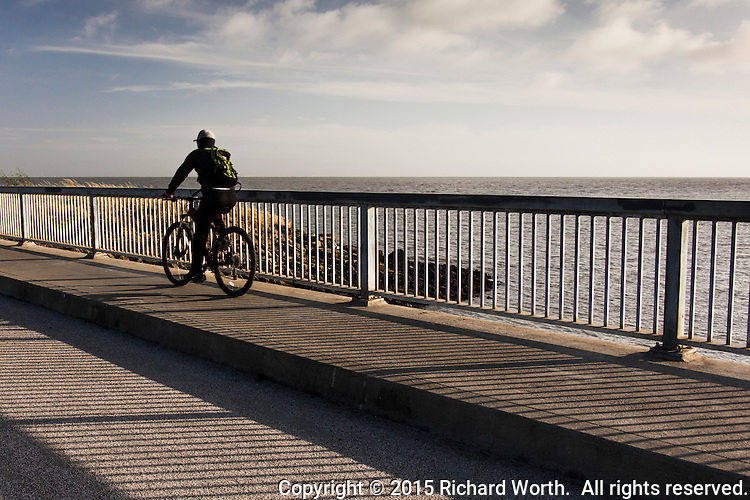 A bicyclist glides across a bridge over a flood control channel that feeds into San Francisco Bay, while the late afternoon sun paints the surface with shadows from the railing.