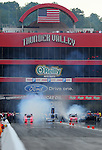 Jun. 18, 2011; Bristol, TN, USA: NHRA funny car driver Cruz Pedregon (left) does a burnout alongside Bob Tasca III during qualifying for the Thunder Valley Nationals at Bristol Dragway. Mandatory Credit: Mark J. Rebilas-