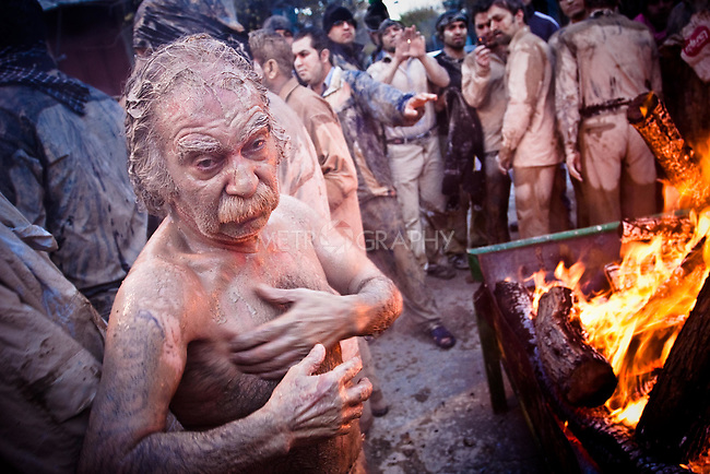 KHORRAMABAD, IRAN : A man dries his muddy body next to a fire...Every year to mark the death of Imam Hussein, Shia Muslims mourn for two days. In Khorramabad and Lorestan in the west of Iran, during the first day of mourning, called Tasooa, women take a vow of silence and go through the streets with the children lighting candles. At 4 am on Ashura, the second day, men cover themselves in mud and then stand in front of a fire until the mud has dried to clay. After this they go to the mosque and pray...Photo by Farhad Babaei/Metrography