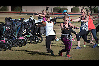 Hillary Cooper, Scottsdale, purple, and the rest of her class work on their upper body strength during their Fit4Mom class at Desert Horizon Park in Phoenix. The class uses portable equipment strollers and park landscape to help moms fit a workout into their busy schedules.