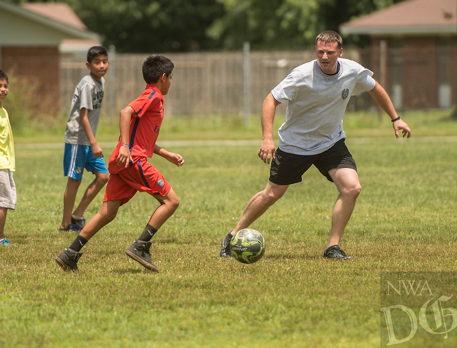 NWA Democrat-Gazette/ANTHONY REYES &bull; @NWATONYR<br /> Juan Barroso, 11, pushes the ball up the pitch as Philip Group, with the Springdale police department, defends Wednesday June 24, 2015 during a soccer game at Jones Elementary School in Springdale. Group and other officers were at the school as part of the Sandlot Program where they help mentor the students through play. The officers open up the gymnasium to the children who play and can eat lunch at the school free of charge.