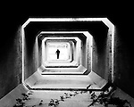 A lone silhouetted man standing at the end of a tunnel of concrete blocks.