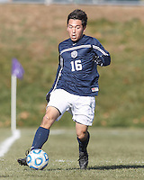 Brandeis defender Josh Hacunda (16) looks to pass. NCAA Division III Sectionals. Williams College (white) defeated Brandeis University (blue/white), 2-0, on Hitchcock Field at Amherst College on November 23, 2013.