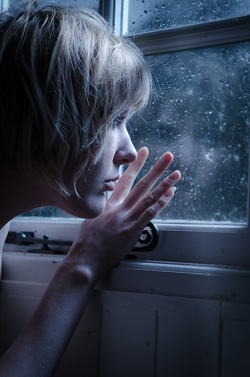 Young adult female with blonde hair looking through window at night