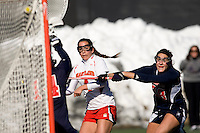 Brandi Jones (4) of Maryland shoots for goal as Danielle Schaevitz (28) of Richmond defends at the practice turf field in College Park, Maryland.  Maryland defeated Richmond, 17-7.