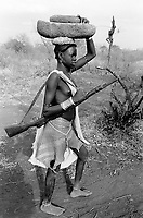 Ethiopia. South Omo Zone. Salamago district. Hana (little village). Bodi tribe. Nomadic. Young girl carrying on her head two stones used to grind cereals and a rifle on her shoulder. She is on her way to Hana for a free distribution of a piece of white tissue (used as clothes) given by the ethiopian government to the Bodi people. Bodi women and girls like to have artistic and stylish haircuts. They wear metal bands on their wrist (silver bracelets) and their dresses are made out of cow's leather. The Bodi tribe is located in the Debub Omo Zone (South Omo Zone) of the Southern Nations, Nationalities and Peoples's région. © 2001 Didier Ruef