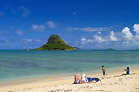 Scenic Mokolii Island (background) more commonly called Chinaman's Hat, lies in the warm blue waters of Kaneohe Bay along Oahu's windward coast. It is one of Oahu's more prominent landmarks. This photo taken from Kualoa Regional Park.