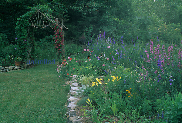 Home garden, with a rustic arbor, rock walls, and various types of flowers.