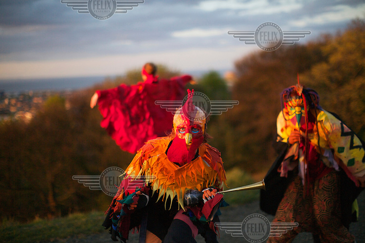 Revellers wearing colourful costumes, including bird masks and 'wings' gather on Cartlton Hill in Edinburgh for the annaul Beltane Fire Festival. The Beltane Festival is an annual event when winter is purged by fire. From sunset on 30 April until early morning, over 300 volunteers create a dramatic reimagining of pagan gaelic folklore surrounded by a crowd of 6000 people. The May Queen arises to herald summer through a battle between elemental forces of order and chaos reaching a climax in the death of the green man in his winter form before bringing him back to life.