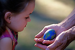 Young girl looking at painted earth egg in the hands of her Grandfather, outside near trees, sunset light.   MR