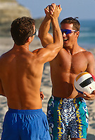 Two volleyball players with hands clasped celebrating