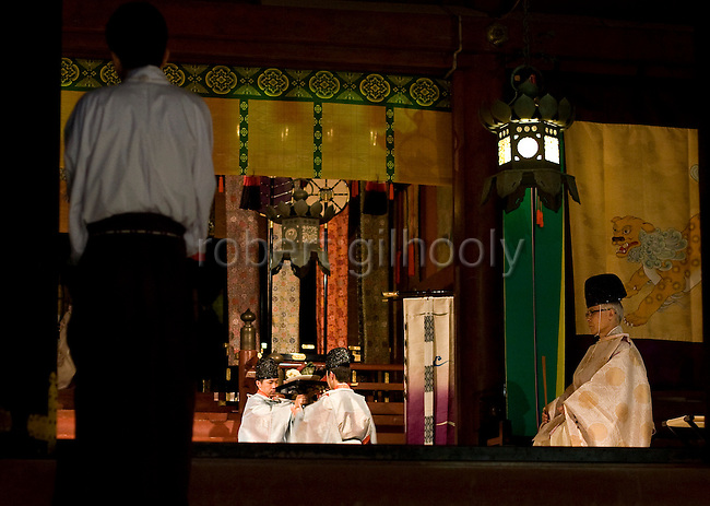 "Priests relay a variety of  goods to be offered to the gods inside the inner sanctuary of the ""Hongu"" main shrine during a ritual held to announce the start of the annual 3-day Reitaisai grand festival at Tsurugaoka Hachimangu shrine in Kamakura, Japan on  14 Sept. 2012.  Photographer: Robert Gilhooly"