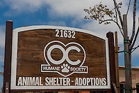 """Wooden sign for the Orange County Humane Society's new shelter on Newland street in Huntingon Beach, CA.  The sign reads """"Animal Shelter - Adoptions"""", and is easily visible from the street as you approach."""