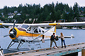 Kenmore Air seaplane at dock and pilot helping passenger with baggage; Friday Harbor, San Juan Island, Washington.