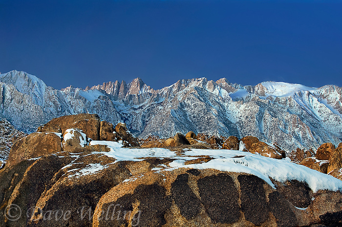 711700288 dawn light on mount whitney mount russell and lone pine peak during a clearing snowstorm with a dusting of fresh snow on the eastern sierras and the granite boulders of the alabama hills in the blm protected lands near lone pine kern county california