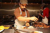 May 26, 2010. Durham, North Carolina.Two employees cook in the kitchen at Dos Perros, a mexican restaurant..