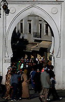 Medina, Tangier, Morocco pictured on December 27, 2009. Crowds in traditional dress walk through a keyhole shaped archway into a street in the Medina. The sun catches the different colours of the headdresses. Tangier, the 'White City', gateway to North Africa, a port on the Straits of Gibraltar where the Meditaerranean meets the Atlantic is an ancient city where many cultures, Phoenicians, Berbers, Portuguese and Spaniards have all left their mark. With its medina, palace and position overlooking two seas the city is now being developed as a tourist attraction and modern port. Picture by Manuel Cohen