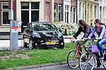 Nederland, Utrecht, 11-07-2011 Fietser passeren een elektrische Nissan Leaf die de de accu's staat op te laden bij een openbaar oplaadpunt in de Oosterstraat. De gemeente wil eind 2012 maximaal 200 oplaadpunten plaatsen in de openbare ruimte en op bedrijfsterreinen. FOTO: Gerard Til /  Hollandse Hoogte