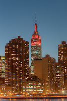 The Empire State Building and other Manhattan buildings at twilight.  The Empire State Building was lit in red in honor of World Aids Day.