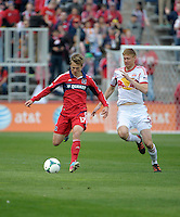 Chicago midfielder Chris Rolfe (17) prepares to pass the ball while being pursued by New York defender Markus Holgersson (5).  The Chicago Fire defeated the New York Red Bulls 3-1 at Toyota Park in Bridgeview, IL on April 7, 2013.