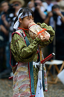 Blowing a conch shell during ceremonies at the Somanakamura shrine, Somanomaoi Festival, Minami-soma City, Fukushima Prefecture, Japan, July 26, 2013. During the four-day-long Somanomaoi Festival members of old samurai families ride horseback through the town in traditional armour.  They also take conduct ceremonies at local shrines, take part in horse races, and compete on horseback to catch a flag launched into the air by fireworks.