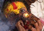 A hindu sadhu (holy man) at the temples of Pashupatinath, lighting up a chilam (hash-pipe) in the late afternoon.<br />