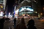 """People on Times Square by night, NYC. A great billboard of the movie """"Flags of our fathers"""" (by Clint Eastwood) can be seen."""