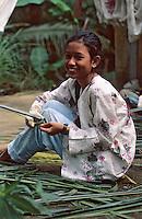 Asie/Singapour/Ile de Ubin: Détail jeune fille coupant les roseaux
