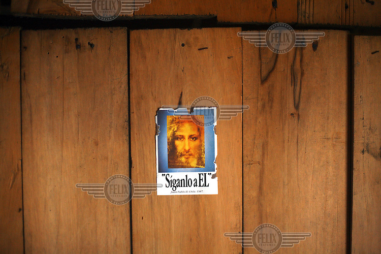 A Jesus sticker on a wall on the island of Teuquelin. This lies off the coast of a larger island called Chiloe that is itself off southern Chile. The only inhabitants of Teuquelin are the Peranchiguay family whose descendants arrived there two hundred years ago. Now only a few elderly people, women and children live there. The men and youth have all left in search of work. Those left behind make a living by harvesting Luga, an algae that is used in the production of shampoo and nappies.
