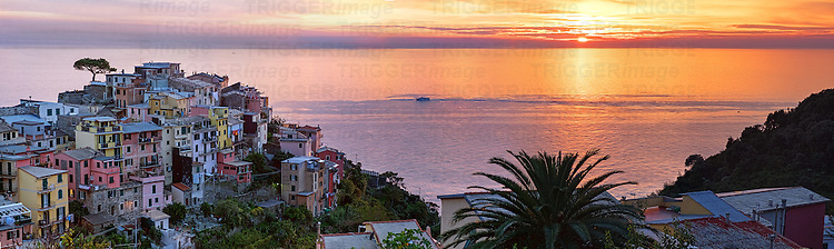 A golden sunset over the Mediterreanean Sea, with the village of Corniglia in the foreground on a hilltop.