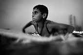 Mahmoud Bakeat, 13, battles with the surf while padlling out from Gaza City, Gaza Strip. Mahmoud began sufing this year and is one of the youngest surfers in Gaza.