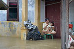 A woman feeds her daughter above floodwaters during November 2014 flooding in Meulaboh in Indonesia's Aceh province. Flooding in the region has grown worse because of climate change and the proliferation of palm oil plantations.
