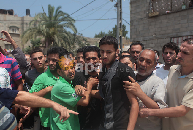Palestinian mourn during the funeral for members of the al-Kelani family in Beit Lahia in the northern Gaza Strip, on July 22, 2014. A series of Israeli air strikes early killed seven people in Gaza, including five members of the same family, emergency services spokesman Ashraf al-Qudra said. The deaths hike the total Palestinian toll to 583 since the Israeli military launched Operation Protective Edge on July 8 in a bid to stamp out rocket fire from Gaza. . Photo by Ashraf Amra