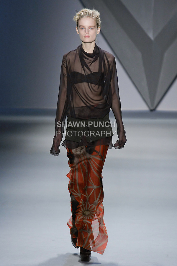 Hanne Gaby Odiele walks runway in a brown silk chiffon long sleeve cowl neck top with plunging back over brown techno stretch strapless bra Tangerine vault print organza floor-length skirt with brown techno stretch zip-front peplum, from the Vera Wang Fall 2012 Vis-a-gris collection, during Mercedes-Benz Fashion Week Fall 2012 in New York.