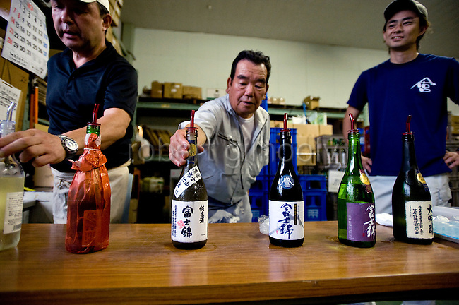 Staff at Fuji-nishiki Sake Brewery display bottles of the brewery's products at the company's brewery in Fujinomiya, Shizuoka Prefecture Japan on 02 Oct. 2012.  Photographer: Robert Gilhooly