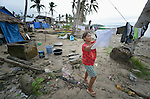 Corazon Graboso hangs her laundry to dry in Bacubac, a seaside neighborhood in Basey in the Philippines province of Samar that was hit hard by Typhoon Haiyan in November 2013. The storm was known locally as Yolanda. Graboso and her family currently live in the temporary shelter behind her. The ACT Alliance has been providing a variety of assistance to survivors here.