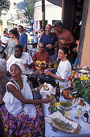 Baiana named Angela Maria selling typical food from Bahia State in front of Bar do Gomes in Santa Teresa quarter, with Roda de samba in the background ( people playing and singing samba in the sidewalk ).