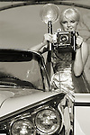 A fashion model holding an old camera