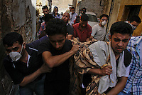 Residents and Free Syria Army soldiers carry the burned bodies of one woman and her two grand daughters after they died from a tank shell which tore through their kitchen in Aleppo's old city.