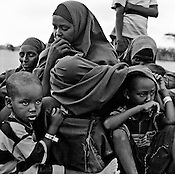 A Somali refugee family wait outside the registration centre at the IFO-1 camp in the Dadaab refugee camp in northeastern Kenya. Hundreds of thousands of refugees are fleeing lands in Somalia due to severe drought and arriving in what has become the world's largest refugee camp. Photo: Sanjit Das/Panos