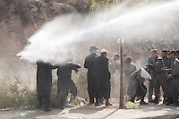 Ultra-Orthodox Jewish man take cover from police water jet in Ramat Beit Shemesh West of Jerusalem on August 12 2013, after dozens of Haredim protest against desecration of ancient graves were discovered at a new housing construction site. Some 14 Ultra-orthodox Jews were arrested. Photo by Oren Nahshon