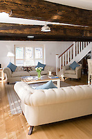 A pair of matching sofas upholstered in natural linen have been arranged on either side of a plain wooden coffee table under the massive ceiling beams of the living room