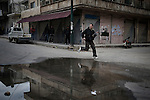 SYRIA - Al Qsair. Free Syrian Army fighter is seen as he run crossing a street in Al Qsair, on February 24, 2012. ALESSIO ROMENZI