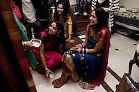 Delhi, India, 20 gennaio 2011. Matrimonio di Sumedha e Sapan. Sumedha attorniata dai parenti, il mattino del matrimonio, durante le celebrazioni prima della funzione. La sorella Suchi lava i piedi di Sumedha, come gesto propiziatorio.
