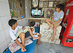 """In the capital of the Philippines, children watch television in their home in the Manila North Cemetery. Hundreds of poor families live in the cemetery, dwelling inside and between the tombs and mausoleums of the city's wealthy. They are often discriminated against, and many of their children don't go to school because they're too hungry to study and they're often called """"vampires"""" by their classmates. With support from United Methodist Women, KKFI--a Filipino NGO--provides classroom education and meals to kids from the cemetery at a nearby church."""