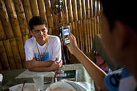 A young boy, an admirer of Pablo Fajardo, takes his picture with a mobile phone. Pablo is the lead attorney for plaintiffs in a class action lawsuit brought against US multinational Texaco (acquired by Chevron in 2001) by more than 30,000 Ecuadorians. The case has been in the Ecuadorian courts since 2003 and relates to the dumping of billions of gallons of toxic materials into unlined pits and Amazonian rivers. In February 2011 the court ruled that Chevron should pay a fine totalling 9.5 billion USD. However, Chevron has stated that the ruling is 'illegitimate and unenforceable' and has started numerous counter proceedings in US courts. There is some doubt as to whether it will be possible to force Texaco to pay the fine.