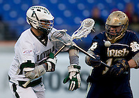 Eric Lusby (12) of Loyola has the ball checked away from him by Kelly McKenna (13) of Notre Dame during the Face-Off Classic in at M&T Stadium in Baltimore, MD