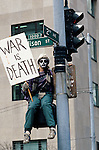 War protester at the Federal Building in downtown Seattle sitting on a traffic light pole holding a War is Death poster wearing a death mask protesting the US involvement in Persian Gulf January 15 deadline 1991 Seattle Washington State USA